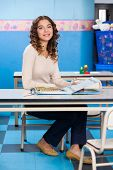 pic of medium-  length hair  - Full length portrait of young teacher with popup book sitting at desk in preschool - JPG