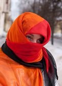 picture of yashmac  - young beautiful woman in red purdah against street - JPG
