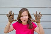 foto of mud  - happy kid girl playing with mud with dirty hands smiling portrait - JPG