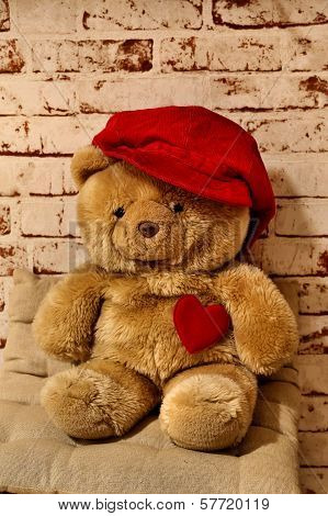 Sweet teddy bear with a heart and a cap