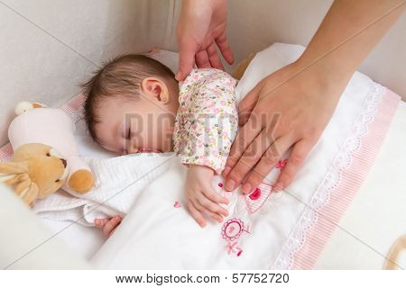 Hands of mother caressing her baby girl sleeping