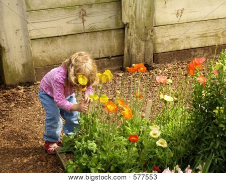 Pequeña niña que huele flores