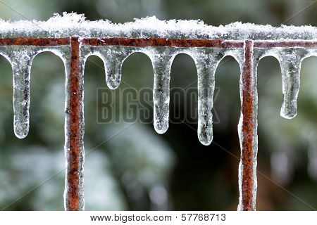 Icicles on a rusted fence after an ice storm.