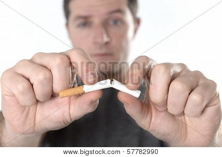 Attractive man breaking cigarette representing quit smoking