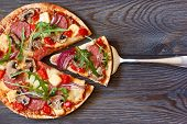image of salami  - Pizza with salami and arugula on a wooden board - JPG