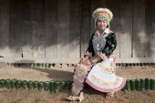 stock photo of hmong  - Portrait Asian woman Laos Hmong in front of wooden house - JPG