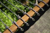 foto of grommets  - Knotted rope along a wooden beam lashing to canvas through metal grommets - JPG