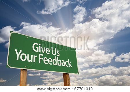 Give Us Your Feedback Green Road Sign with Dramatic Clouds and Sky.