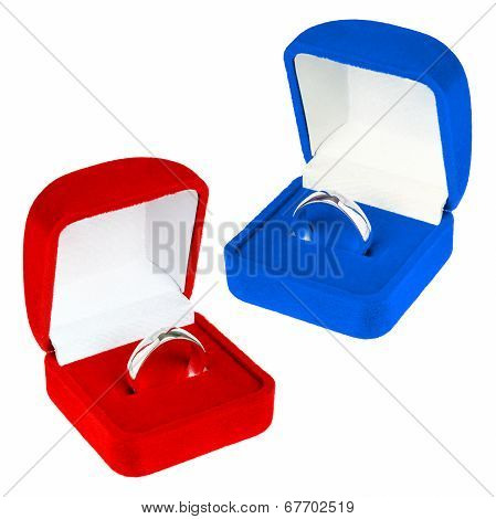 Red and blue velvet boxes with platinum ring