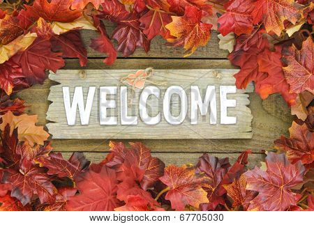 Colorful fall leaves border weathered welcome sign