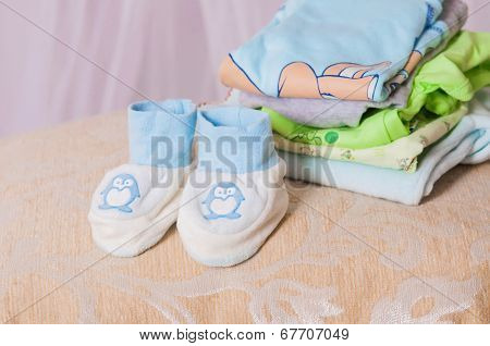 baby booties and clothes folded