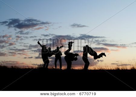 Silhouette of a bunch of people jumping