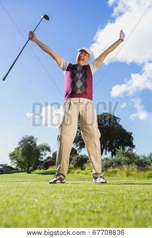 Excited golfer cheering and looking at camera on a sunny day at the golf course