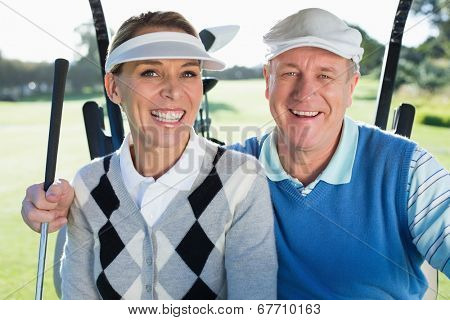 Happy golfing couple sitting in golf buggy smiling at camera on a sunny day at the golf course
