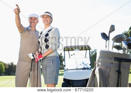 Happy golfing couple pointing with golf buggy behind on a sunny day at the golf course