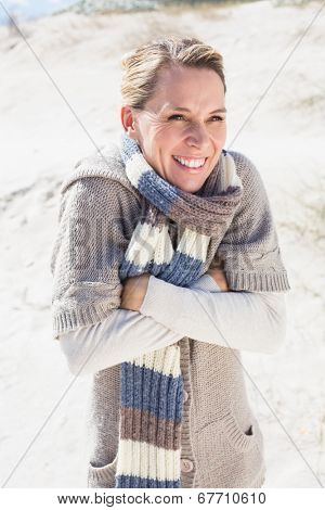 Attractive shivering blonde standing on the beach on a bright but cool day