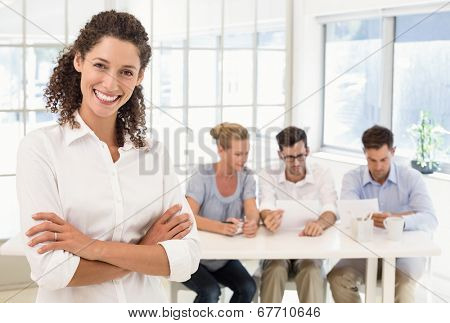 Casual businesswoman smiling at camera with team behind her in the office