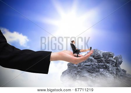 Businesswoman sitting on swivel chair with feet up in large hand against large rock overlooking bright sky