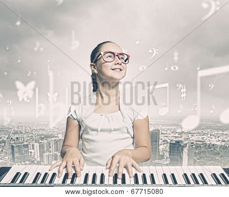 Young girl sitiing at digital piano with red glasses