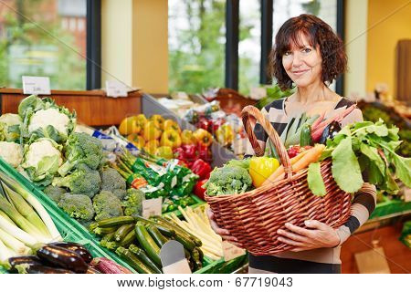 Elderly smiling woman buying fresh vegetables in a supermarket