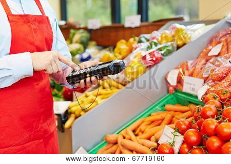 Hand of salesperson using mobile data acquisition terminal in a supermarket