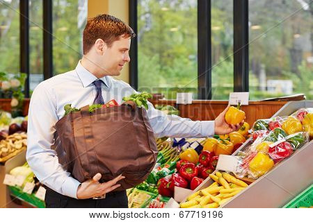 Smiling businessman buying fresh vegetables in an organic food store