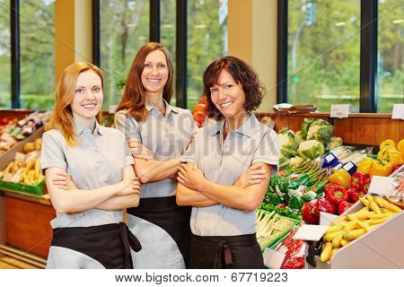 Group of three happy sales women in a supermarket