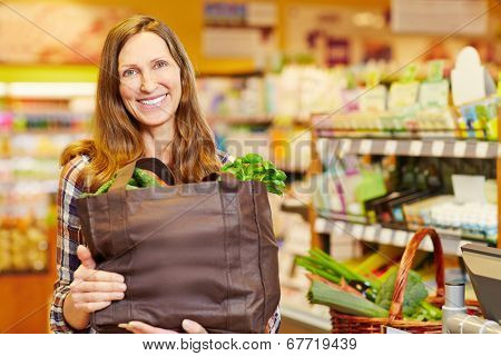 Smiling woman holding full shopping bag with vegetables in organic food store