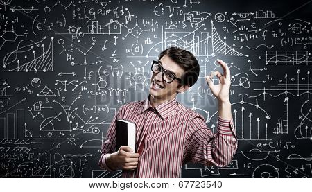 Young funny man in glasses against chalk blackboard