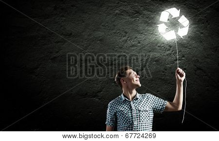 Young handsome man with recycle balloon against dark backdrop