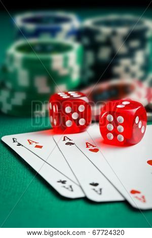 the red casino dice and poker cards on green table