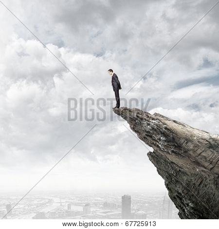Businessman standing on edge of hill and looking down