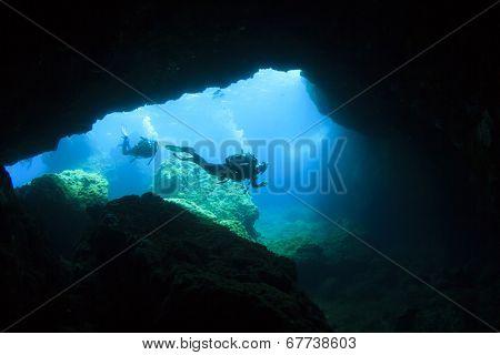 Scuba Divers enter underwater cave