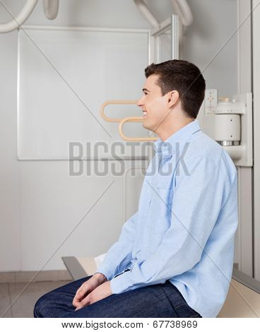 Side view of young man smiling while sitting on x-ray table at laboratory