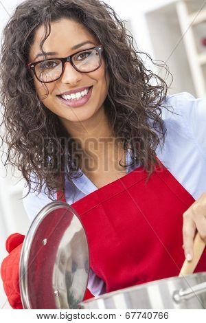 A beautiful girl or young woman looking happy wearing red apron, glasses & cooking in her kitchen at home