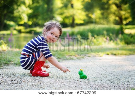 Beautiful Little Girl In Red Rain Boots Playing With Rubber Frog