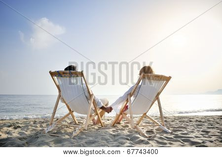 Romantic Couple On Deckchair Relaxing Enjoying Sunset On The Beach