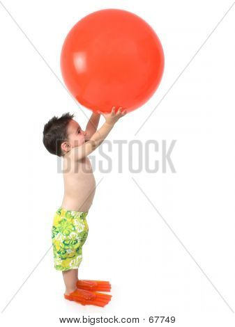 Adorable Boy Ready To In Swim Gear With Giant Orange Ball Over W