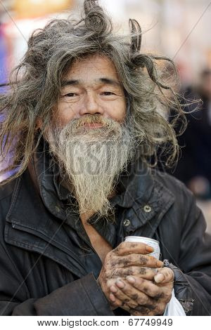 TOKYO,JAPAN, November 25 : Cheerful tramp  holding a drink can, posing in the street near the Shibuya crossroad in Tokyo, Japan, on November 25, 2011