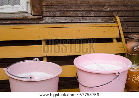 Two Pink Pail Full Fresh Cow Milk On Wooden Bench