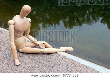 Wooden pose puppet sitting on stone, outdoors