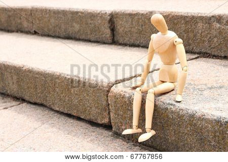 Wooden pose puppet sitting on stair, outdoors