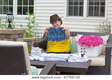 Joyful Granny Folding Her Granddaughters Clothes