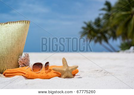 Summer beach bag with coral,towel,sunglas ses and coral on sandy beach