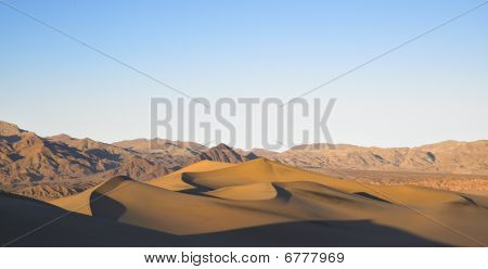 Sand Dunes With Mountains In Background