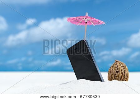 Mobile phone and cocktail umbrella on the beach with the sea in the background