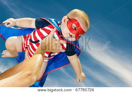 Happy Baby Boy Wearing Superhero Costume Flying In The Sky