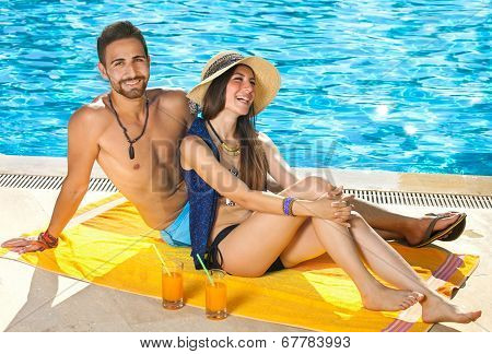 Attractive Couple Relaxing Alongside A Pool