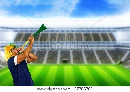 Brazilian fan at stadium playing vuvuzela for celebrating a brazil team goal