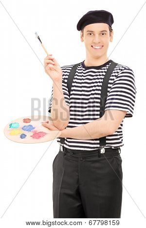 Male artist with paintbrush and a color palette posing isolated on white background
